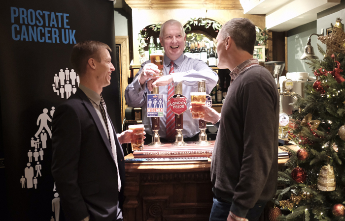 Men share a pint of Fuller's Wise Men beer, brewed to raise money and awareness of Prostate Cancer UK.