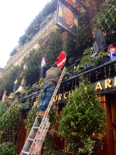 Putting up Christmas decorations at Fuller's pub The Churchill Arms in London